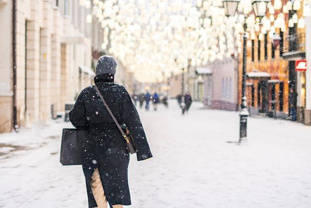 Person zu fuß in den straßen der stadt in der wintersaison unter schneefall b