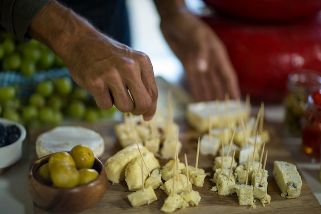 Personal, das ein stück käse auf holzbrett im lebensmittelgeschäft arrangiert