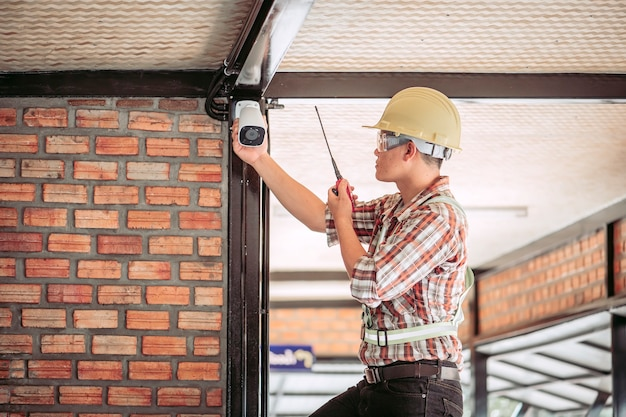 Personal in arbeitskleidung überprüfung des im gebäude verwendeten cctv-systems.