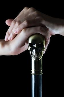 Personal mit dem Schädel, der in der Frauenhand auf schwarzem Hintergrund hält
