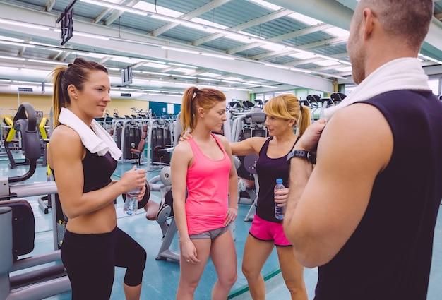 Personal trainer, der eine traurige junge frau nach einem harten trainingstag im fitnessstudio ermutigt