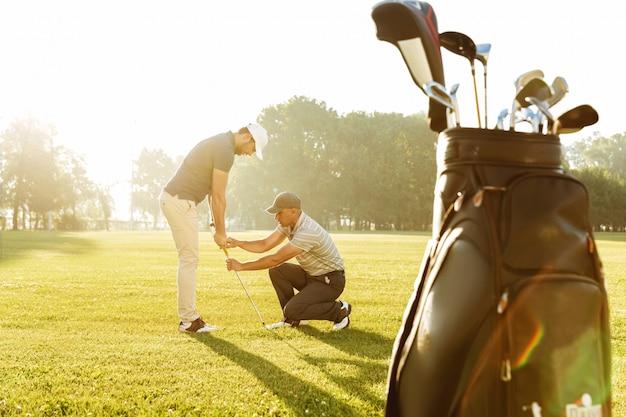 Personal trainer, der einem jungen männlichen golfer eine lektion erteilt