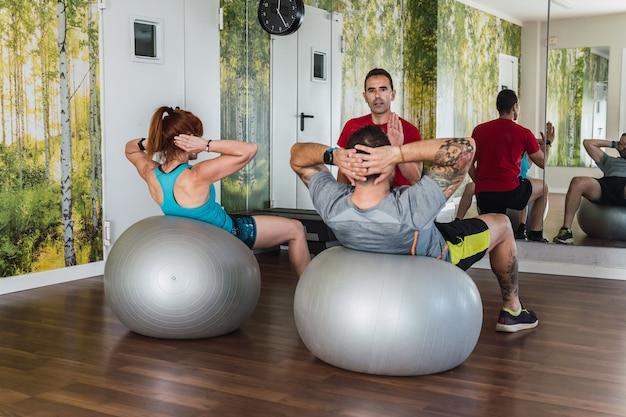 Personal trainer, der einer gruppe von menschen in einem fitnessstudio pilates-übungen erklärt.