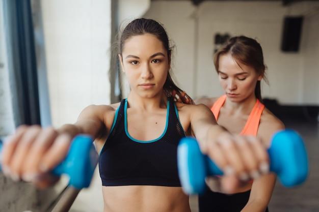 Personal trainer der jungen frau, der beim training im fitnessstudio hilft. frau macht übungen