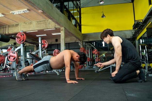Personal trainer, der übergewichtigen mann hilft liegestütze in einem fitnessstudio, fitness, gewichtsverlust konzept.