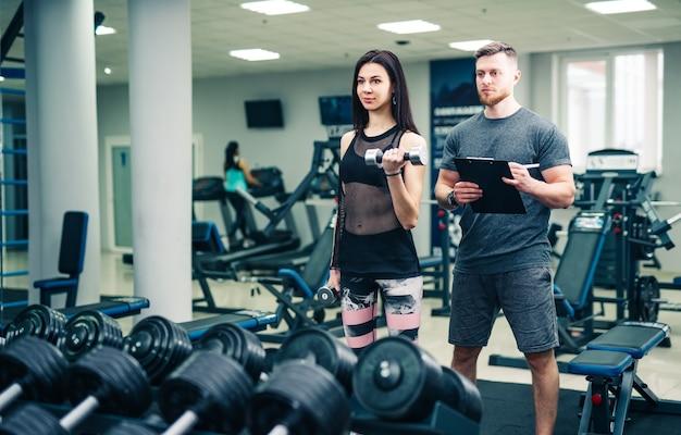 Personal trainer hilft frau, die mit schweren hanteln arbeitet. persönlicher fitnesstrainer. personal training.