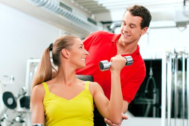 Personal trainer im fitnessstudio für bessere fitness