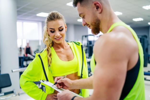 Personal trainer mit einem ordner, der mit kundenfrau in einem fitnessstudio arbeitet