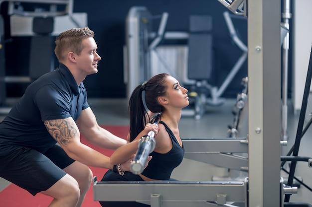 Personal trainer und fit frau arbeiten mit langhantel