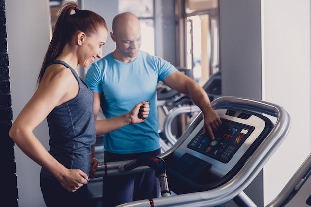 Personal training mit einem trainer auf einem laufband