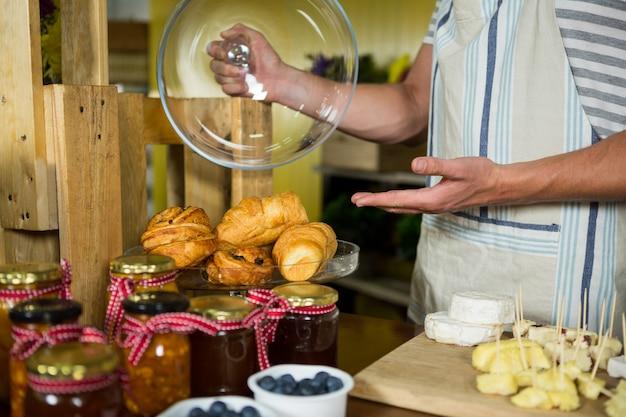 Personal zeigt croissant an der theke
