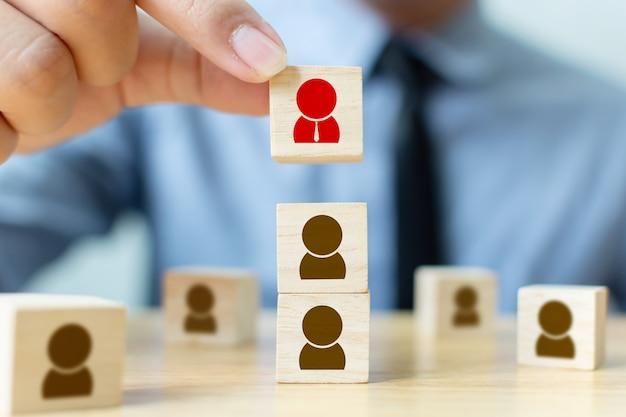 Personalmanagement- und einstellungsgeschäft bauen teamkonzept auf. geschäftsmannhand, die hölzernen würfelblock auf die oberseite setzt