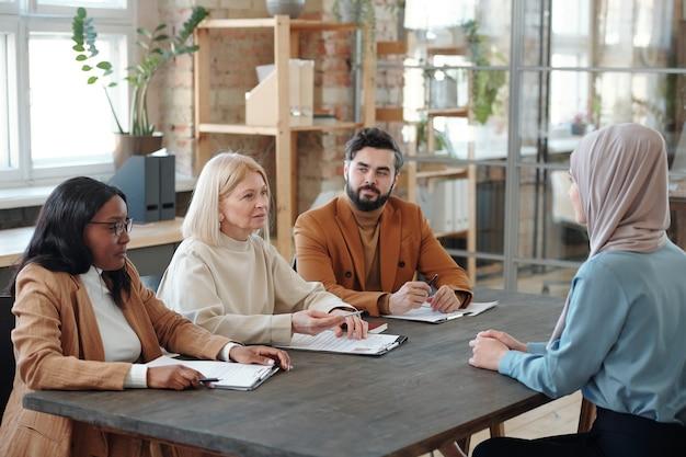 Personalmanager und abteilungsleiter sitzen am tisch mit lebensläufen eines arabischen stellenbewerbers und sprechen mit ihr während des meetings
