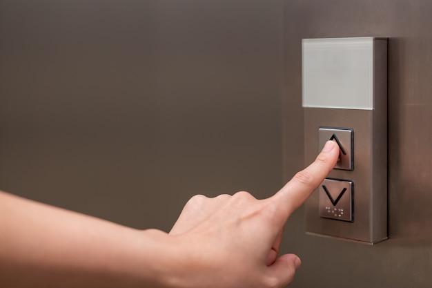 Personen, die den knopf im aufzug drücken und mit dem zeigefinger den ersten stock auswählen.