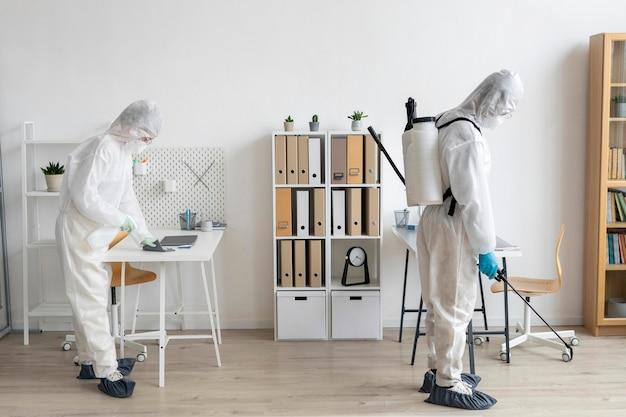 Personen, die schutzausrüstung zur desinfektion eines gefährlichen bereichs tragen