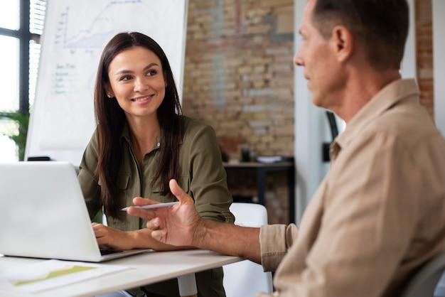 Personen, die während eines meetings ein digitales gerät verwenden