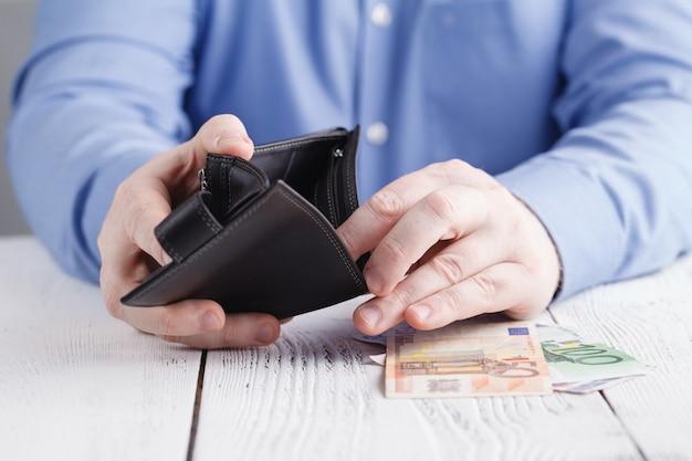 Personen-, geschäfts-, finanz- und geldkonzept - nahaufnahme von geschäftsmannhänden, die offenes portemonnaie mit euro-bargeld halten