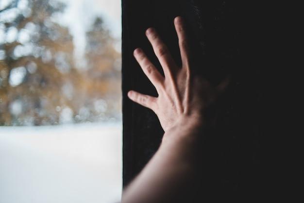 Personen linke hand am fenster