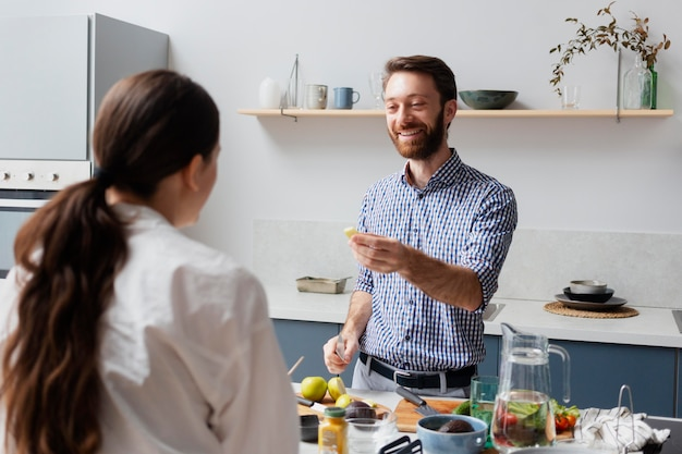 Personen mit mittlerer aufnahme, die drinnen essen zubereiten