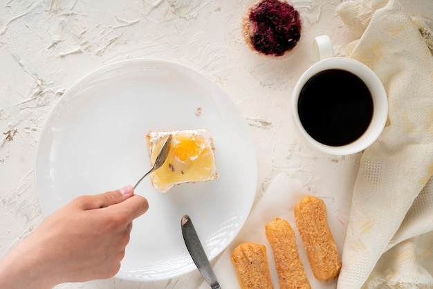 Personen übergeben grifflöffel und lebensmittelmesser und essen süßen kuchen auf einer platte, geschirr, draufsichten