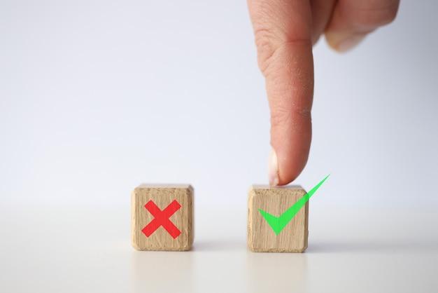 Personenfinger zeigt auf einen würfel mit grünem häkchen