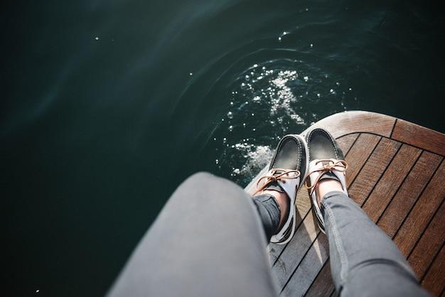 Personenfüße auf dem boot, das tagsüber auf dem meer segelt