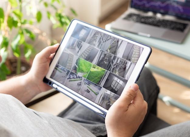 Personenhand, die ein smartphone mit mehreren kameraansichten von bürostandorten hält