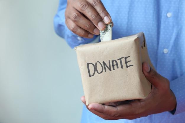 Personenhand, die geld an eine wohltätigkeitsorganisation spendet