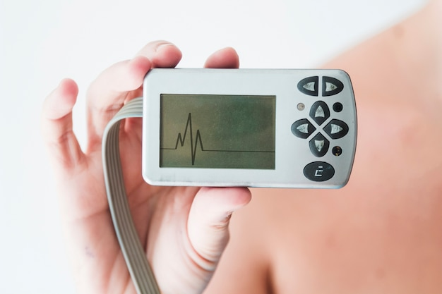 Personenhand, die monitor mit kardiogramm hält