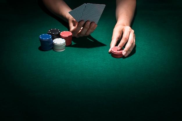 Personenhand, die pokerkarte im kasino spielt