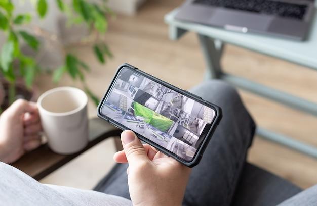 Personenhand, die smartphone mit mehreren kameraansichten der überwachung von bürostandorten hält