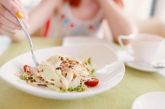 Personenhand hält gabel in einem teller mit salatfrau, die leckeres essen im café-gericht mit eierkirsche isst, um...