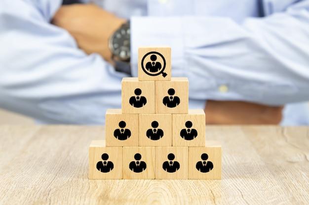 Personenikone auf würfelholzspielzeugblöcken gestapelt in einer pyramidenform