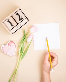 Personenschreiben auf papier nahe aufschrift des 12. mai