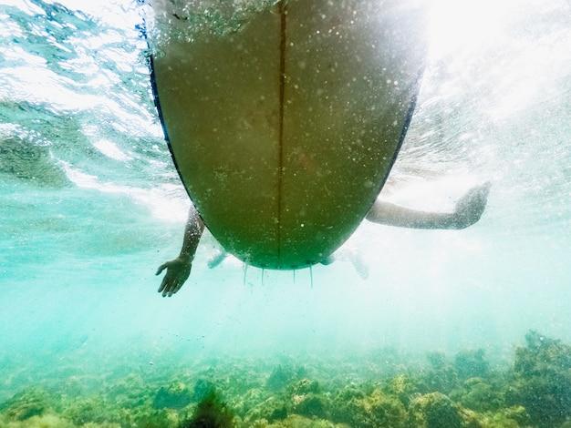 Personenschwimmen auf surfbrett im blauen meer