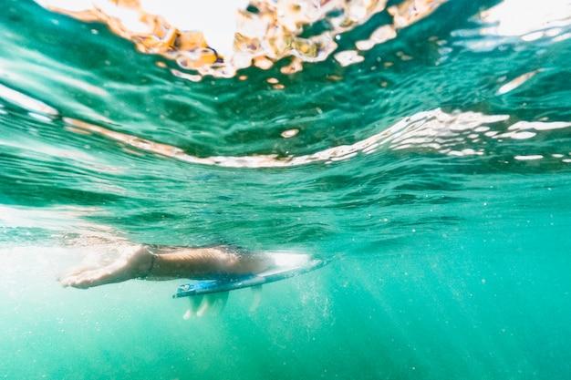 Personenschwimmen auf surfbrett im blauen ozean