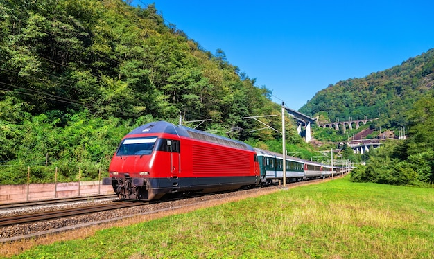 Personenzug fährt den gotthardpass in den schweizer alpen hinunter
