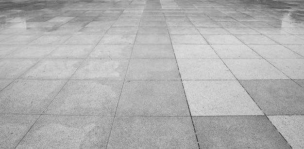Perspektivenansicht von monotonem grey brick stone aus den grund für straßen-straße. bürgersteig, fahrstraße, straßenbetoniermaschinen, pflaster im weinlese-design, das quadratischen muster-beschaffenheits-hintergrund ausbreitet