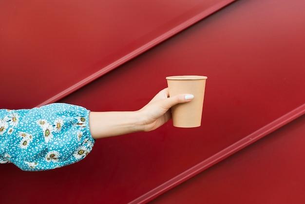 Perspektivenhand der linken ansicht mit köstlichem heißem kaffee