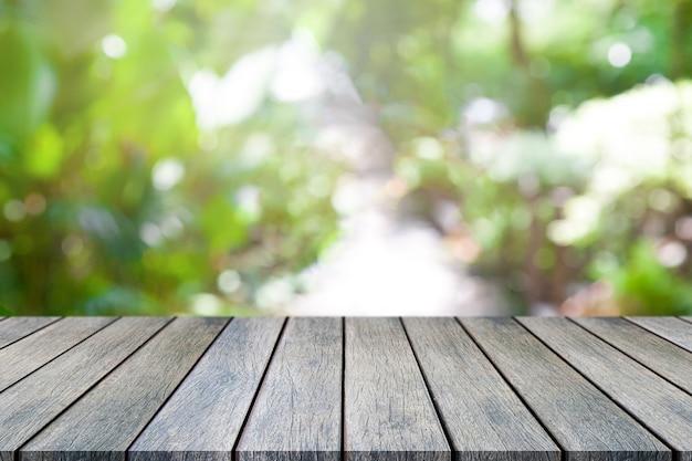 Perspektivenholztisch auf die oberseite über natürlichem hintergrund der unschärfe