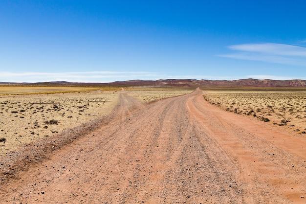 Perspektivische ansicht der bolivianischen schotterstraße, bolivien. blick auf das andenplateau