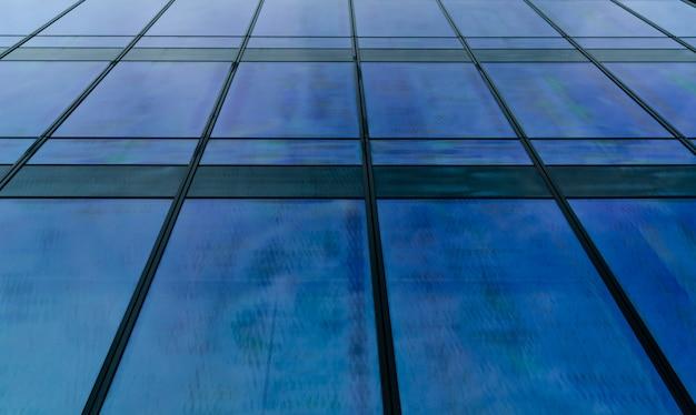 Perspektivische ansicht des abstrakten hintergrunds des modernen futuristischen glasgebäudes. außenansicht der architektur des büroglasgebäudes. reflexion in transparentem glas des geschäftsgebäudes.