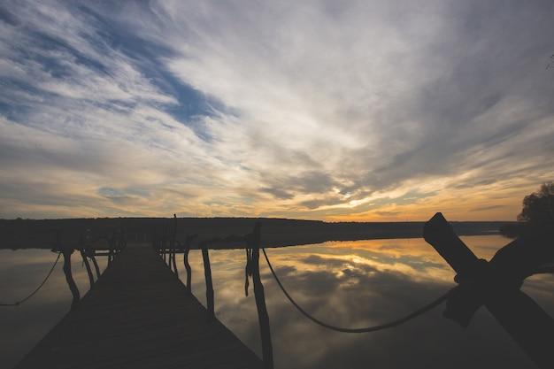 Perspektivische ansicht eines hölzernen piers auf einem fluss bei sonnenuntergang