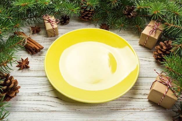 Perspektivische ansicht. runde keramik der leeren platte auf hölzerner weihnachtsoberfläche.
