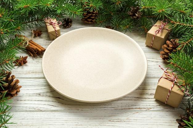 Perspektivische ansicht. rundes keramisches der leeren platte auf hölzernem weihnachtshintergrund. feiertagsabendessenteller mit dekor des neuen jahres