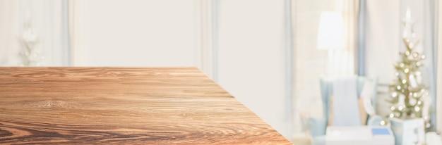 Perspektivischer holztisch mit verschwommenem weihnachtsbaum verzieren lichterkette im wohnzimmer zu hause. panorama-holzarbeitsplatte für produktanzeige