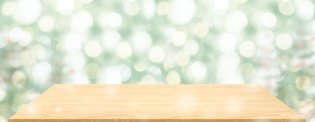 Perspektivischer holztisch mit verschwommenem weihnachtsbaum verzieren lichterkette
