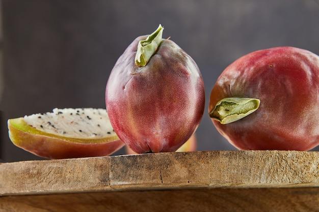 Peruanische apfelkaktusfrüchte ganz und auf holzständer auf grauem brett geschnitten. wissenschaftlicher name cereus repandus