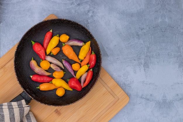 Peruanische chilischoten in verschiedenen farben auf grauer oberfläche