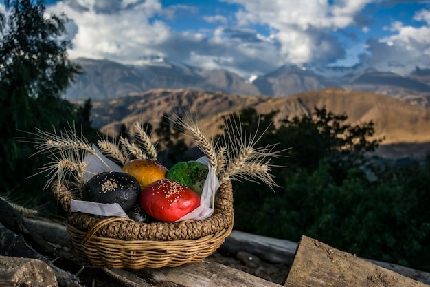 Peruanisches andenmädchen posiert mit brot in berglandschaft mit brot im korb